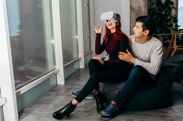 Pareja joven experimentando realidad virtual (vr) en el salón
