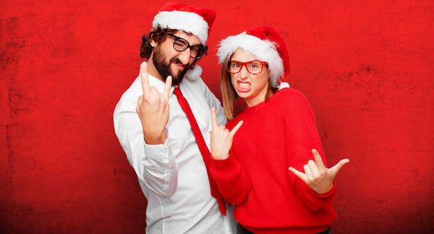 Pareja joven expresando el concepto de navidad. pareja y fondo en diferentes capas.