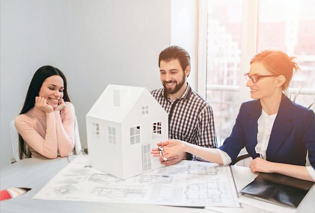 Pareja joven familia compra alquiler propiedad inmobiliaria. agente dando consulta a hombre y mujer. firma de contrato para la compra de casa o piso o apartamentos. él sostiene una maqueta de la casa en las manos.