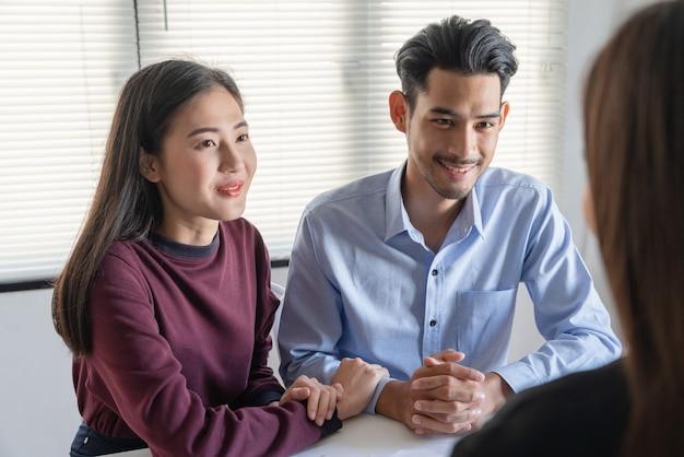 Pareja joven de la familia hablando con el agente de bienes raíces de la propiedad sobre el contrato de compra del contrato de préstamo hipotecario