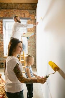 Pareja joven, familia haciendo reparación de apartamentos juntos ellos mismos. madre, padre e hijo haciendo remodelación o renovación de la casa. concepto de relaciones, movimiento, amor. preparación de la pared para papel tapiz