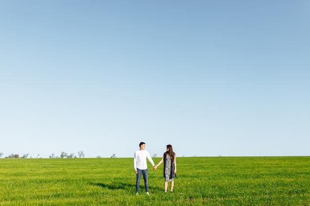 Una pareja joven, feliz y amorosa, de pie en un campo verde, contra el cielo por las manos, y se disfrutan