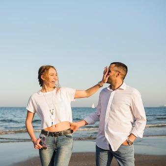 Pareja joven feliz burlando en la playa contra el cielo azul