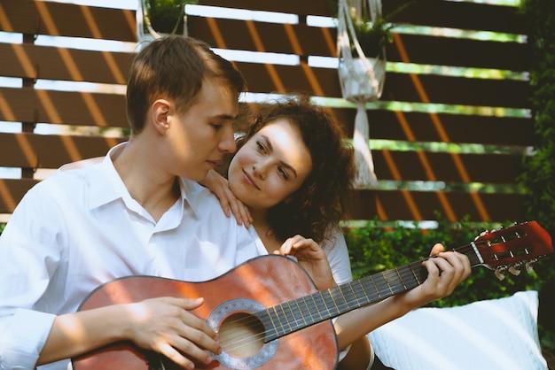 Pareja joven feliz en el hombre del amor que toca la guitarra mientras que la mujer que mira a un hombre en la terraza exterior