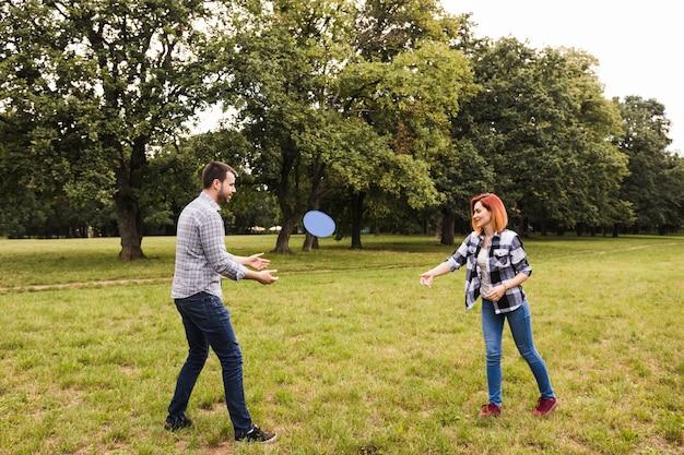 Pareja joven feliz jugando con disco volador en el jardín