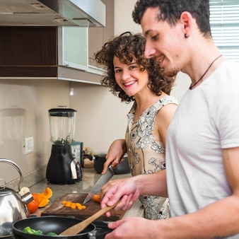 Pareja joven feliz preparando la comida en la cocina