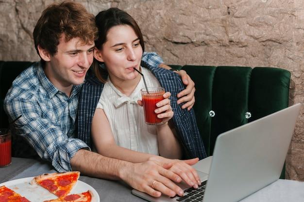Pareja joven feliz en el restaurante mirando el portátil