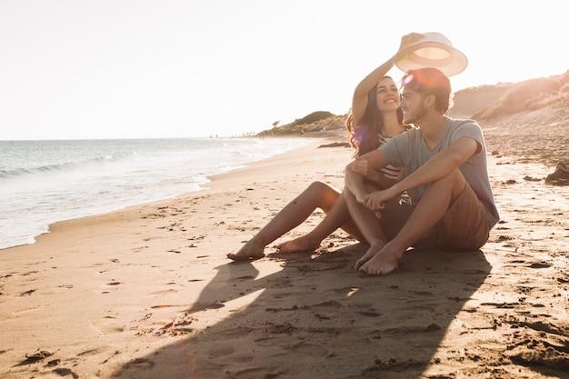 Pareja joven feliz sentada a lado del mar