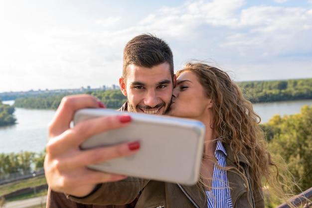Pareja joven feliz tomando fotos selfie cerca del río