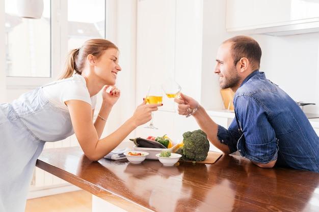Pareja joven feliz tostado de las copas con ensalada fresca en la mesa