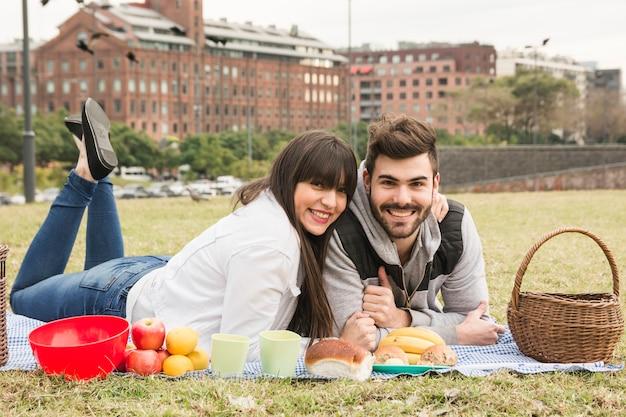 Pareja joven feliz tumbado en la manta con muchos bocadillos saludables en picnic