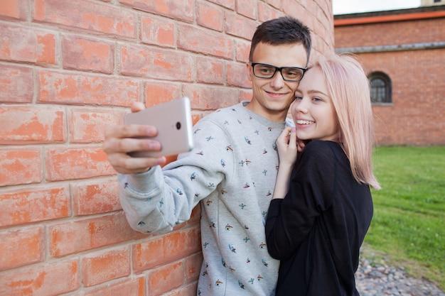 Pareja joven fotografiando un selfie con smartphone.