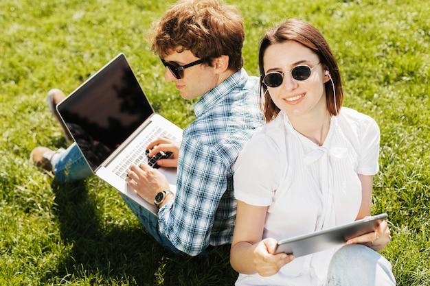 Pareja joven freelance trabajando al aire libre