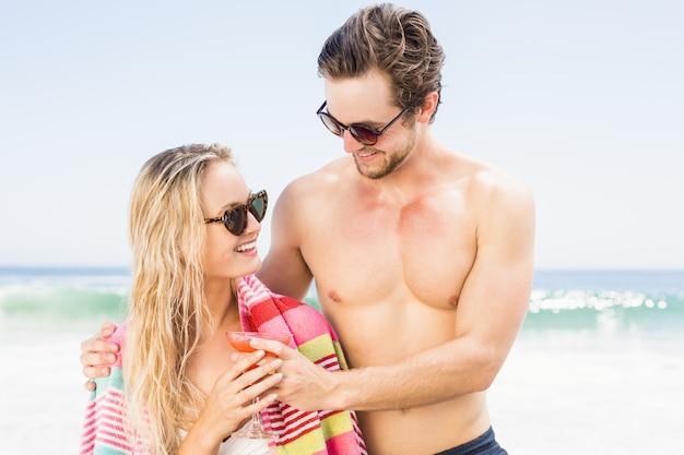 Pareja joven en gafas de sol abrazando en la playa