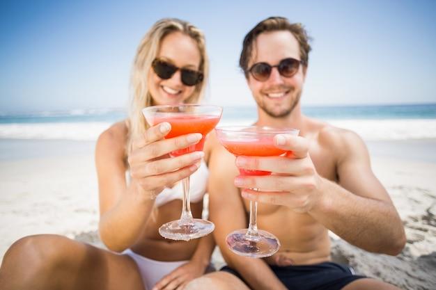 Pareja joven en gafas de sol mostrando copa de cóctel en la playa