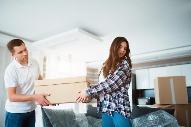 Pareja joven con gran caja de cartón en el nuevo hogar. casa móvil.