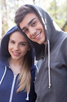Pareja joven con una gran sonrisa llevando sudaderas con capucha