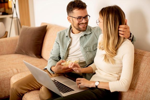 Pareja joven guapo usando laptop juntos mientras está sentado en el sofá en casa