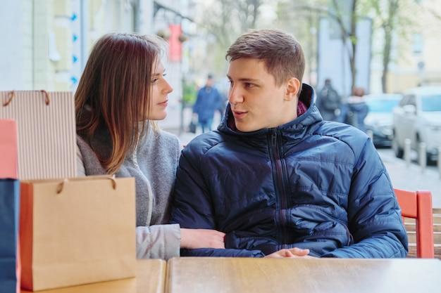 Pareja joven hablando con bolsas de compras en street cafe