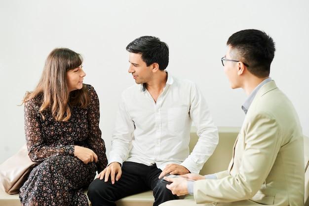 Pareja joven hablando entre sí mientras está sentado en el sofá en consulta con el empresario en la oficina