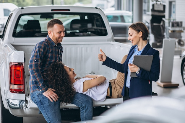 Pareja joven hablando con un vendedor en una sala de exposición de automóviles
