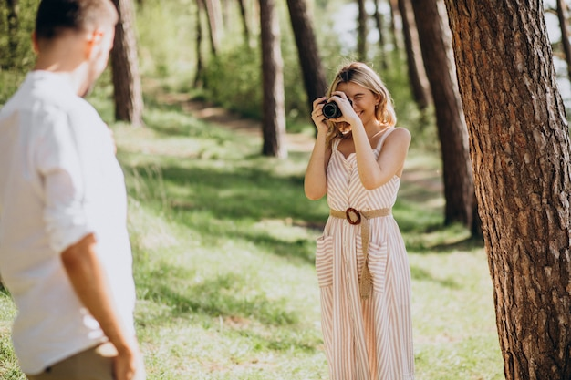 Pareja joven haciendo fotos en el bosque