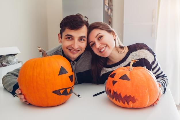 Pareja joven haciendo jack-o-lantern para halloween en la cocina. feliz hombre y mujer prepararon calabazas para vacaciones