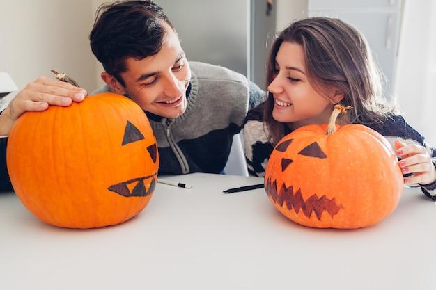 Pareja joven haciendo jack-o-lantern para halloween en la cocina. hombre y mujer comparando sus calabazas