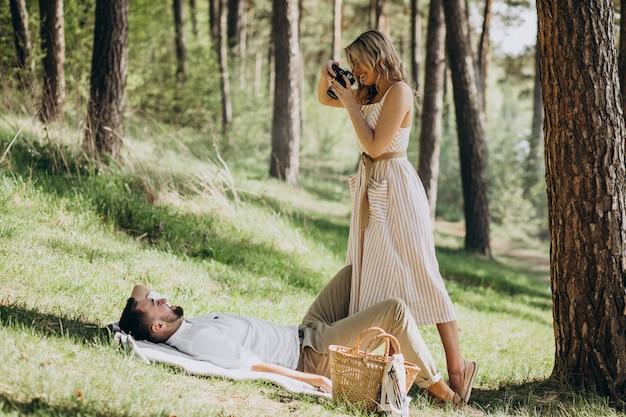 Pareja joven haciendo un picnic en el bosque