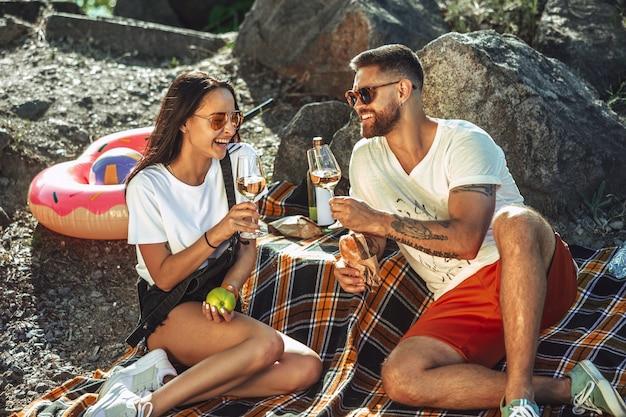 Pareja joven haciendo un picnic en la orilla del río en un día soleado. mujer y hombre pasando tiempo juntos en la naturaleza. divertirse, comer, jugar y reír. concepto de relación, amor, verano, fin de semana.