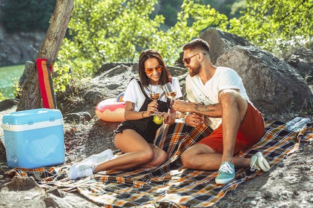 Pareja joven haciendo un picnic en la orilla del río en un día soleado.