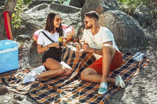 Pareja joven haciendo un picnic en la orilla del río en un día soleado