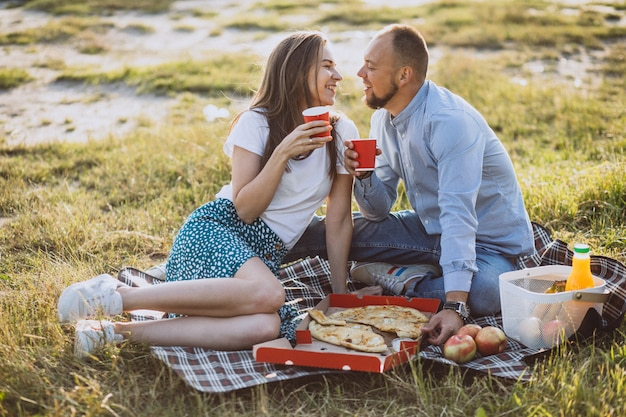 Pareja joven haciendo un picnic con pizza en el parque