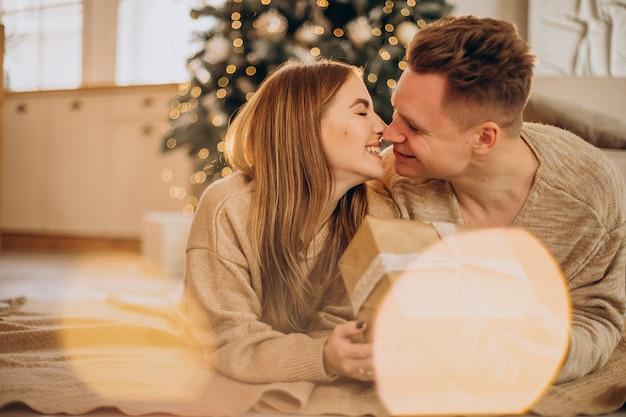 Pareja joven haciendo regalos el uno al otro por el árbol de navidad
