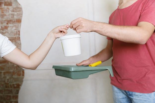 Pareja joven haciendo reparación de apartamentos juntos ellos mismos. hombre y mujer casados haciendo remodelación o renovación de la casa. concepto de relaciones, familia, amor. pintando la pared juntos y riendo.