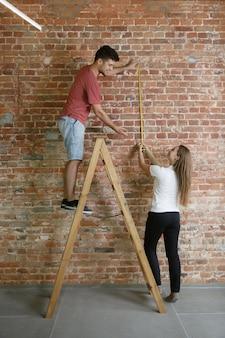 Pareja joven haciendo reparación de apartamentos juntos ellos mismos. hombre y mujer casados haciendo remodelación o renovación de la casa. concepto de relaciones, familia, mascota, amor. medición de pie en escalera con el metro.