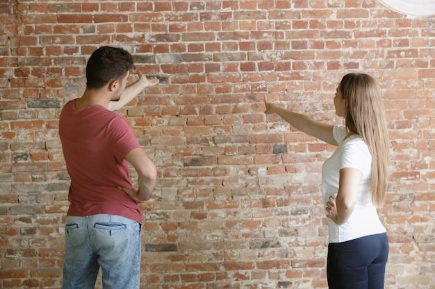 Pareja joven haciendo reparación de apartamentos juntos ellos mismos. hombre y mujer casados haciendo remodelación o renovación de la casa