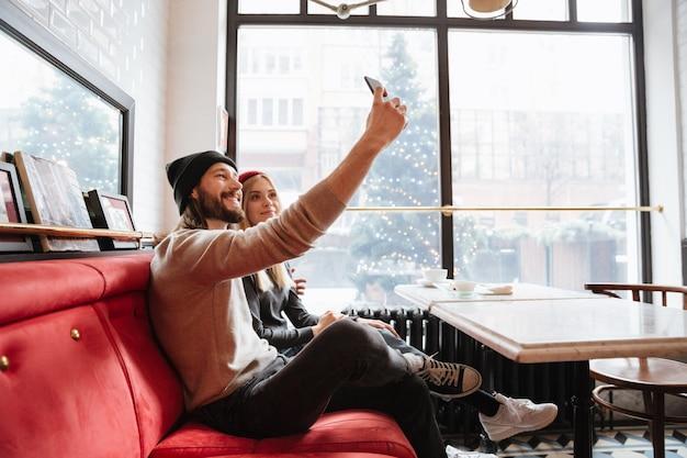 Pareja joven haciendo selfie en café