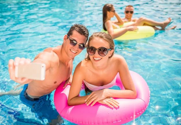 Pareja joven está haciendo selfie mientras se divierten en la piscina.