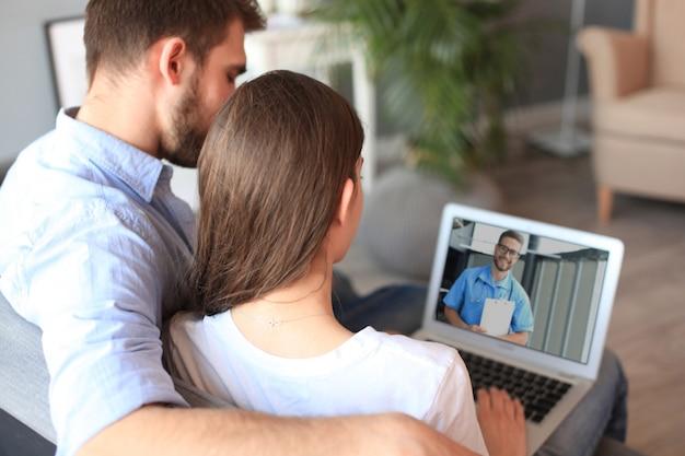 Pareja joven haciendo videoconferencia con médicos en portátil. coronavirus.