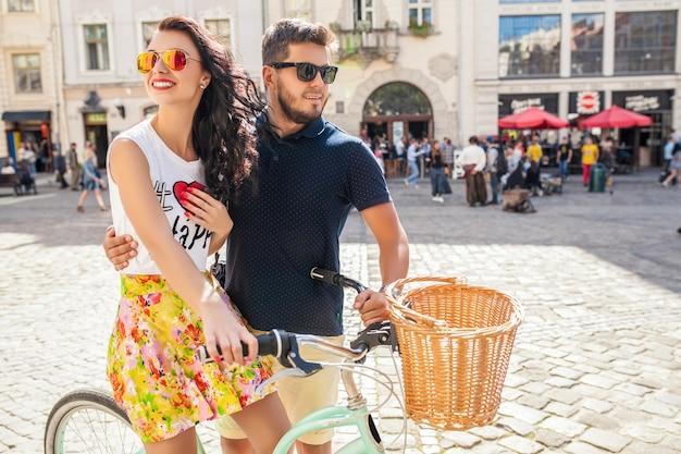 Pareja joven hermosa hipster enamorada caminando con bicicleta en la calle de la ciudad vieja