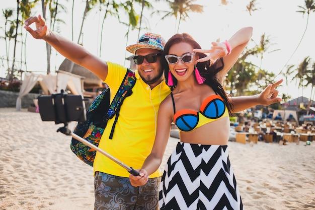 Pareja joven hermosa hipster enamorada en la playa tropical, tomando fotos selfie en teléfono inteligente, gafas de sol, atuendo elegante, vacaciones de verano, divirtiéndose, sonriendo, feliz, colorido, emoción positiva