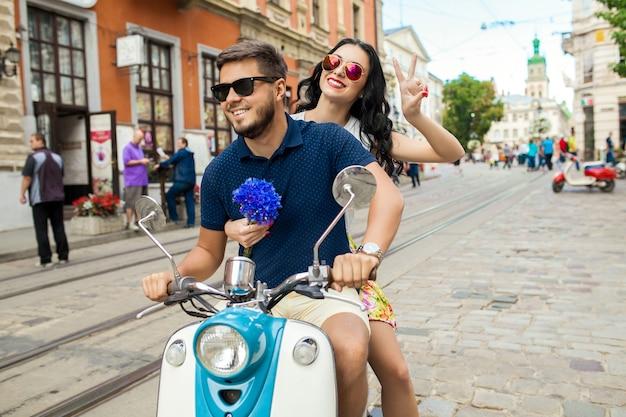 Pareja joven hermosa hipster montando en moto calle de la ciudad