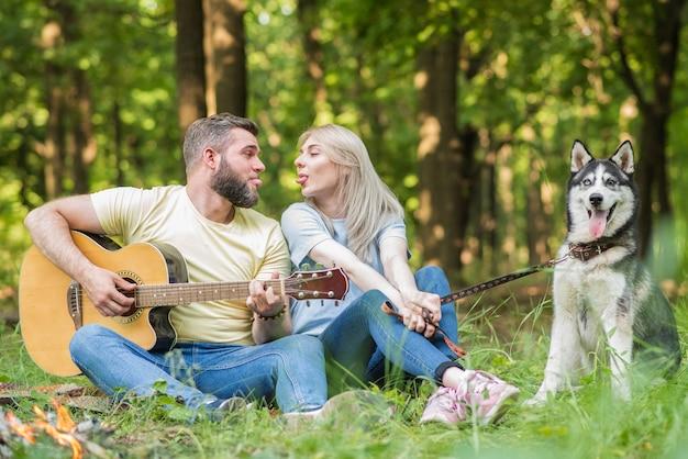 Pareja joven y hermosa relajarse en la naturaleza con un perro a la guitarra
