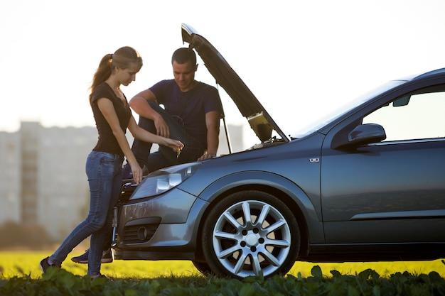 Pareja joven, hombre guapo y mujer atractiva en el coche con el capó abierto comprobando el nivel de aceite en el motor con varilla medidora sobre fondo de cielo despejado.
