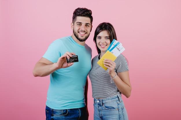 Pareja joven hombre y mujer con boletos de avión y tarjeta de crédito