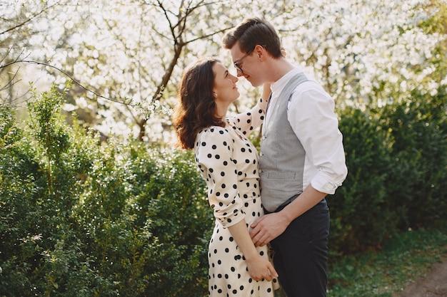 Pareja joven hombre y mujer en un jardín floreciente