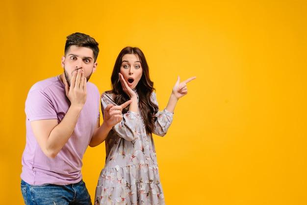 Pareja joven hombre y mujer sorprendido señalando copyspace