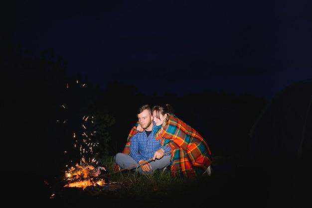 Pareja joven hombre y mujer trevelers sentado cerca de la carpa turística brillante, ardiendo fogata, en la cima de la montaña