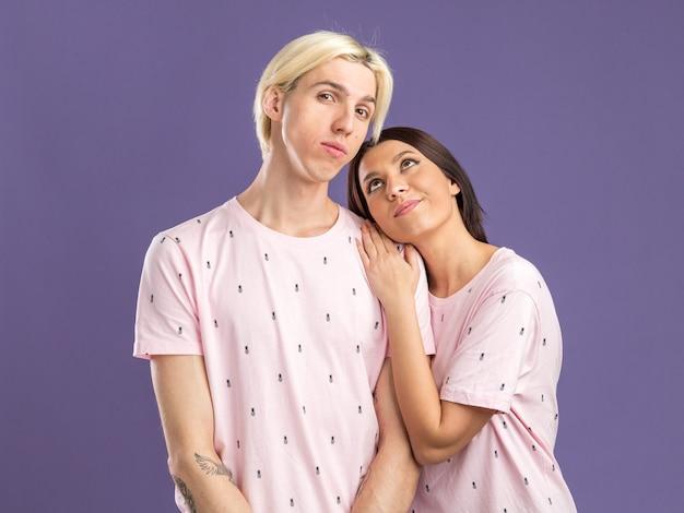 Pareja joven hombre serio mujer complacida en pijama hombre mirando al frente mujer manteniendo la mano sobre el hombro del hombre mirándolo aislado en la pared púrpura